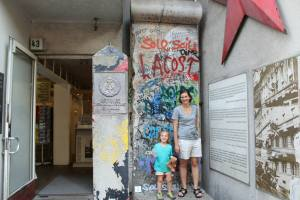 Standing in front of a piece of the Berlin wall